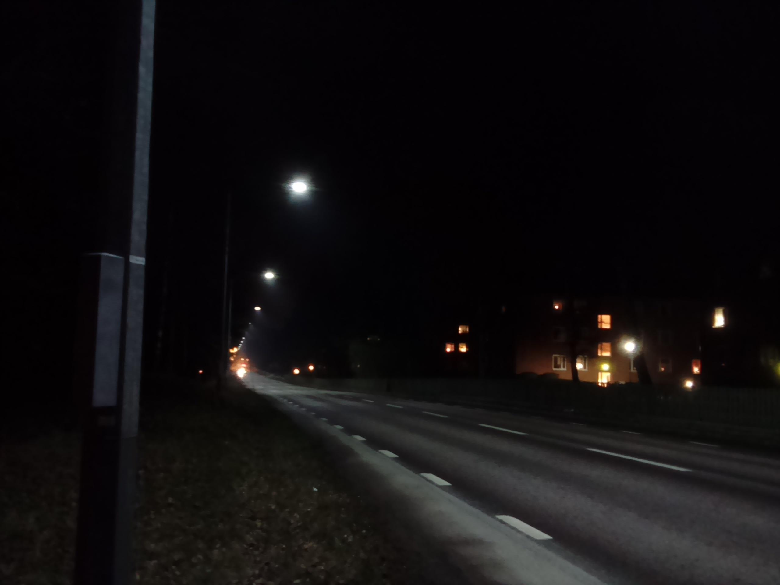 Vi kan jämföra med en kilometerlång sträcka utmed Norra Vägen i Nybro, med samma mobilkamera opch samma väderlek under samma kväll. LED-belysningen utgör en några år gammal teststräcka och är tydligt kall både för blotta ögat och för kameran. Som synes ansluter så gul natriumbelysningen. Vid östra infarten till Nybro finns för övrigt en långre sträcka med gul-orange LED-belysning, som är tydligt varmvit och omöjlig att skilja från natrium högtrycksljus.