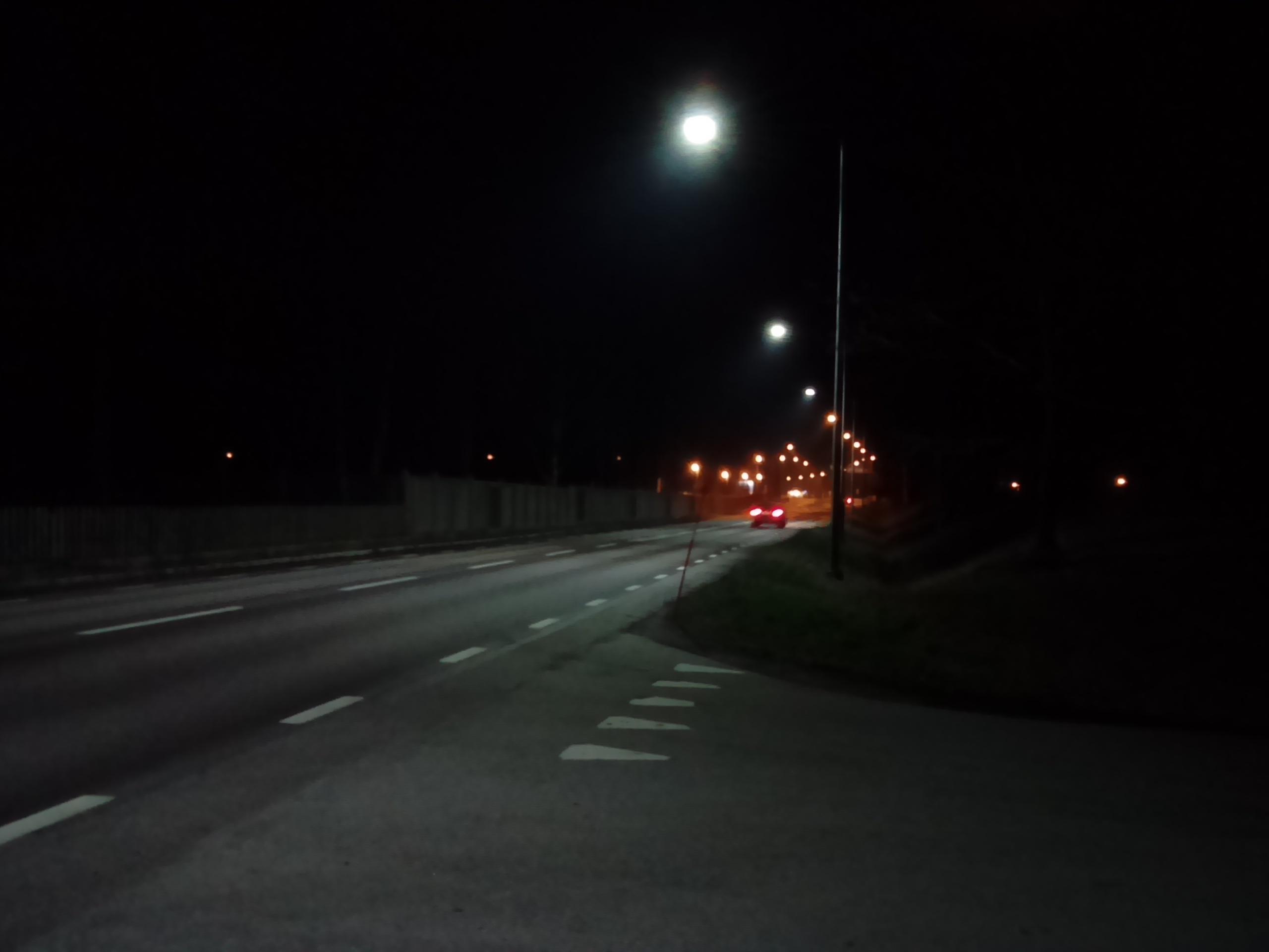 En vy åt andra håller av Norra Vägen där övergången mellan kallvit LED och natrium högtryck syns tydligt.